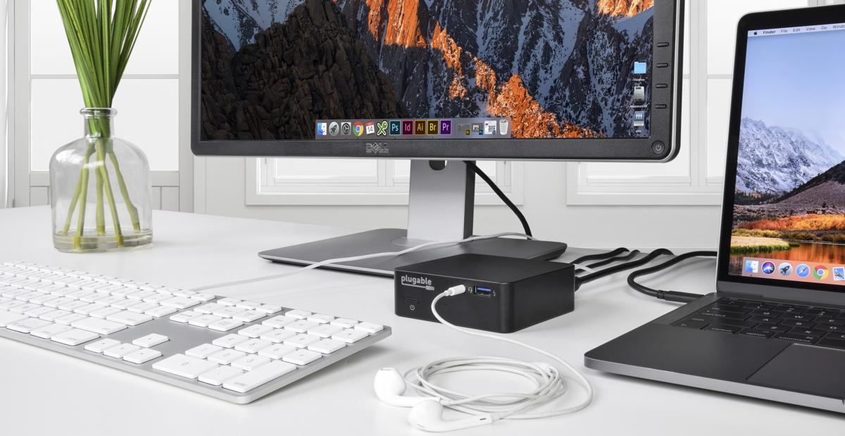 Plugable UD-CAM dock on a desk connected to keyboard, mouse, laptop, and headphones